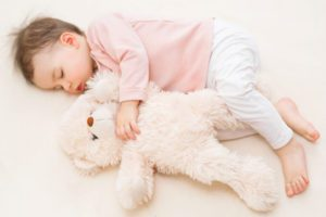 Sleeping beautiful baby toddler girl with a fluffy teddy bear on the bed